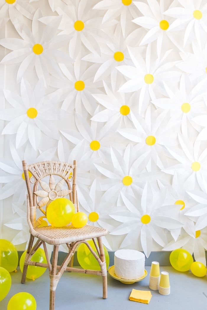 wall full of daisies, wooden chair, yellow balloons around, bedroom wall decor, yellow cake stand