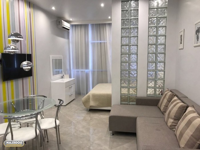 grey sofa, small glass round, dining table, white chairs, tiled floor, how to arrange furniture