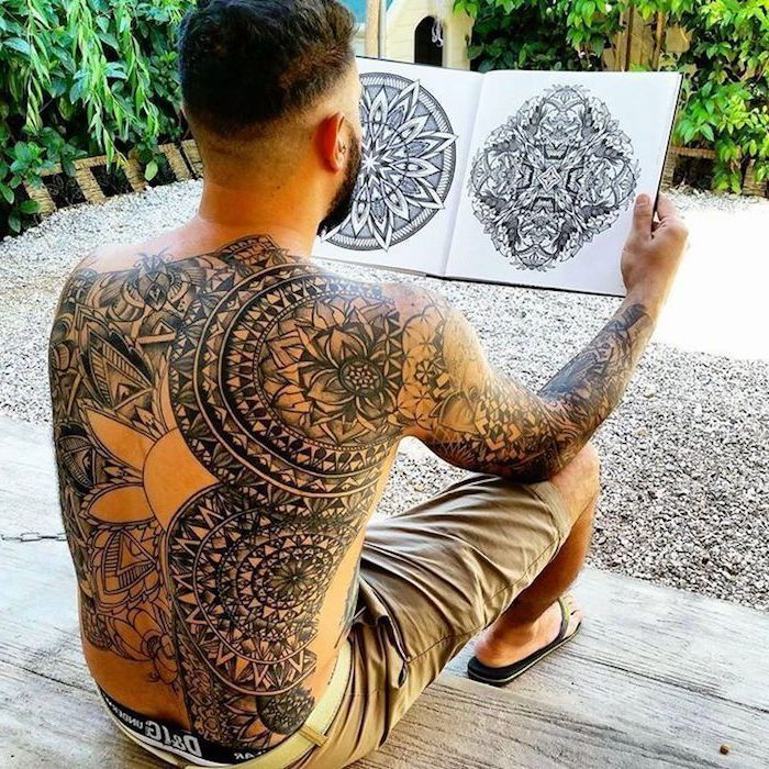 whole back tattoo, sleeve tattoo, man sitting on wooden steps, holding a sketchbook, small mandala tattoo