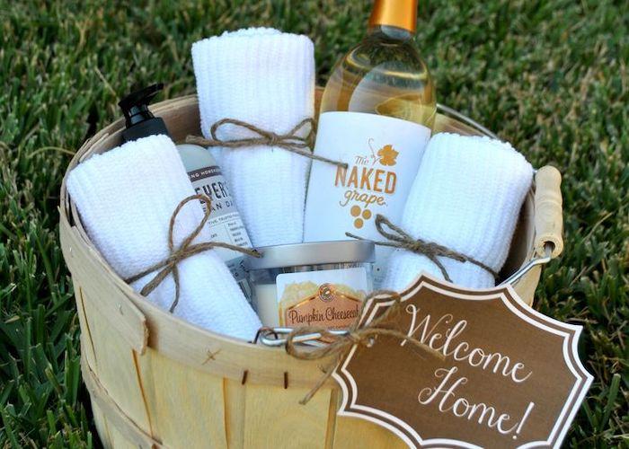 wooden basket, wine and towels inside, good housewarming gifts, diy gift basket