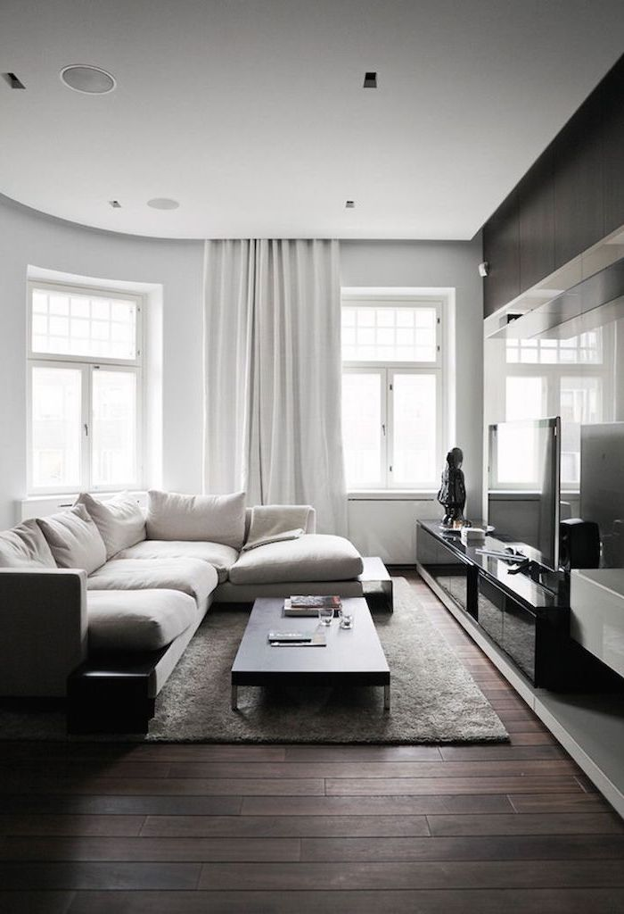 white corner sofa, how to decorate a small living room, small coffee table, dark wooden floor, white curtains