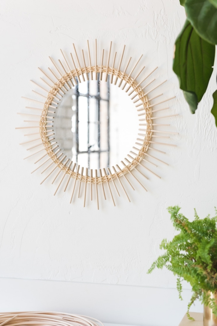 round mirror, frame made out of wooden sticks, large wall decor, hanging on a white wall