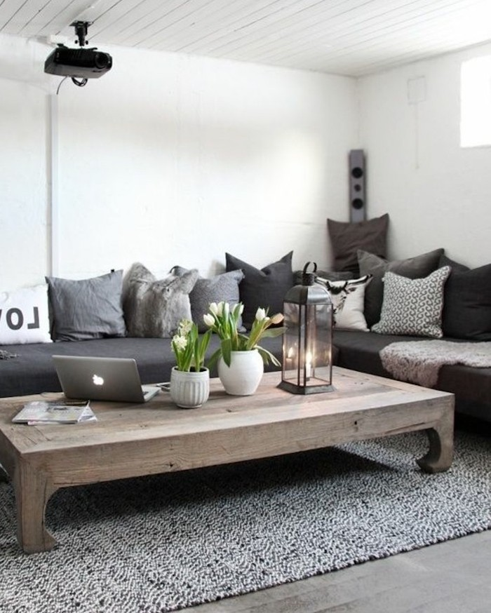 large wooden table, grey corner sofa, lots of throw pillows, grey carpet, popular living room colors