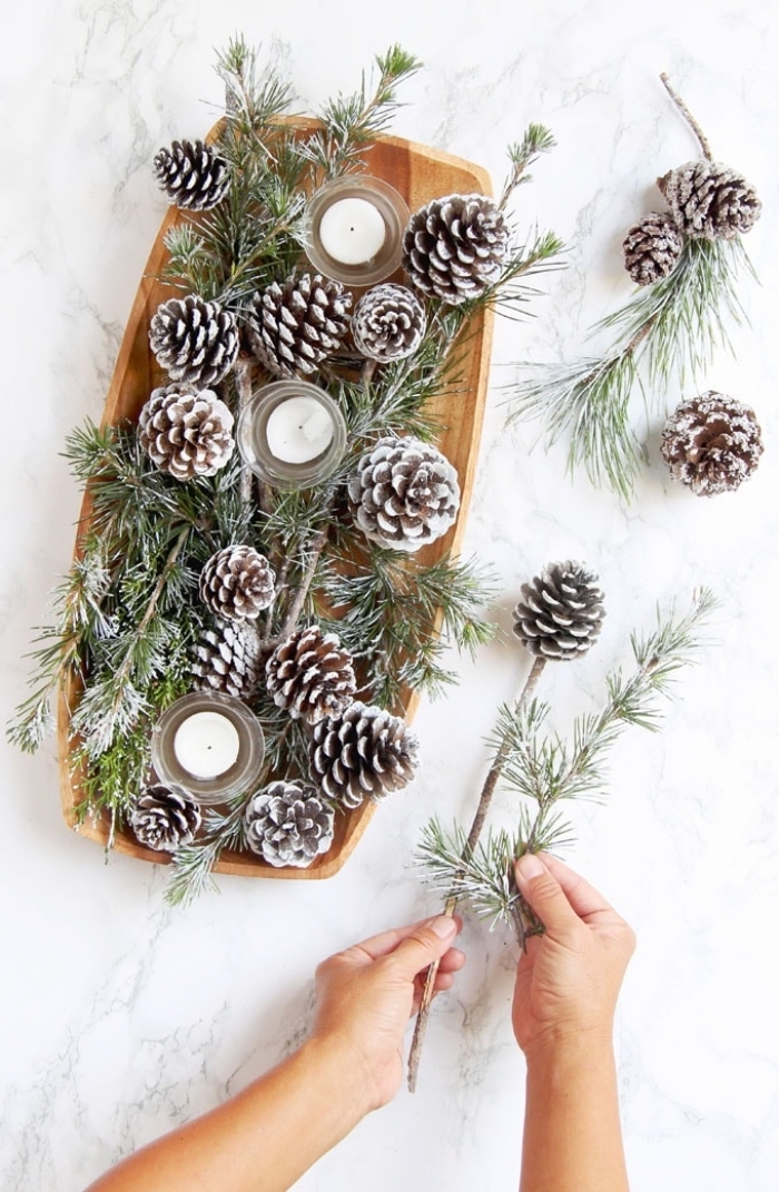 wooden tray, full of pine cones, candles and pine tree branches, fall flower arrangements, marble countertop