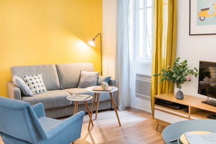 yellow accent wall, grey sofa, how to decorate a small living room, blue armchair, small wooden coffee tables