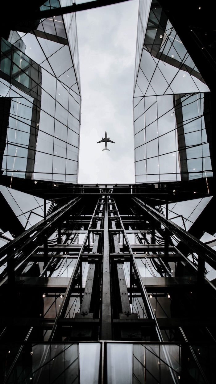airplane in the sky, flying over a glass building, cute backgrounds