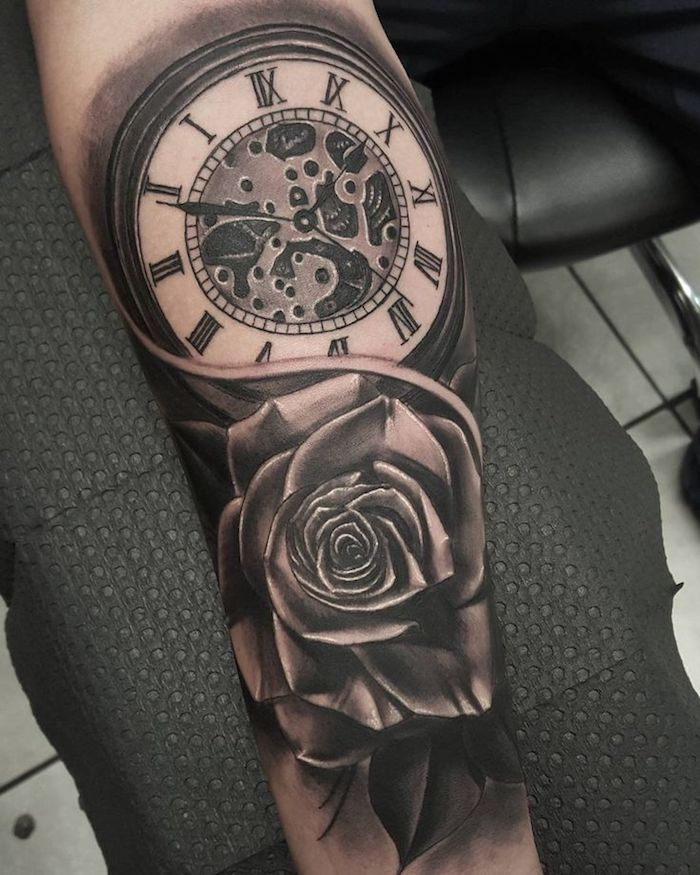 large watch with roman numerals, rose underneath, small tattoos for men, black paper
