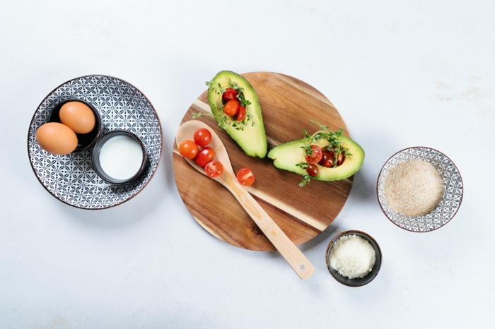 halved avocados and cherry tomatoes, eggs and breadcrumbs, avocado fries recipe, placed on white surface