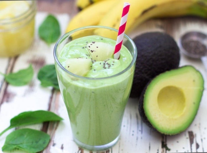 avocado and spinach, peanut butter banana smoothie, on a wooden table, red and white paper straw