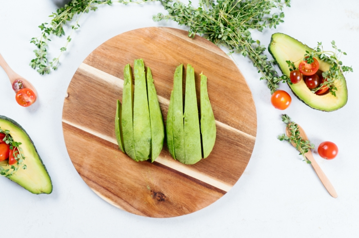 avocado slices, placed on round wooden cutting board, avocado fries recipe, cherry tomatoes around them