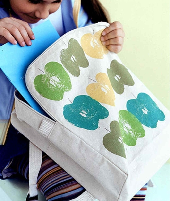 white backpack, apple prints on it, green blue and yellow, prek learning games, little girl holding it