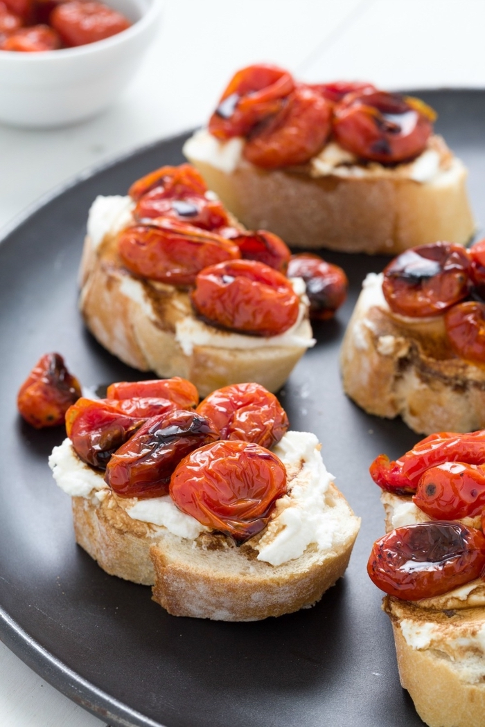 bread slices, baked cherry tomatoes on top, cream cheese, vegan hors d oeuvres, black plate