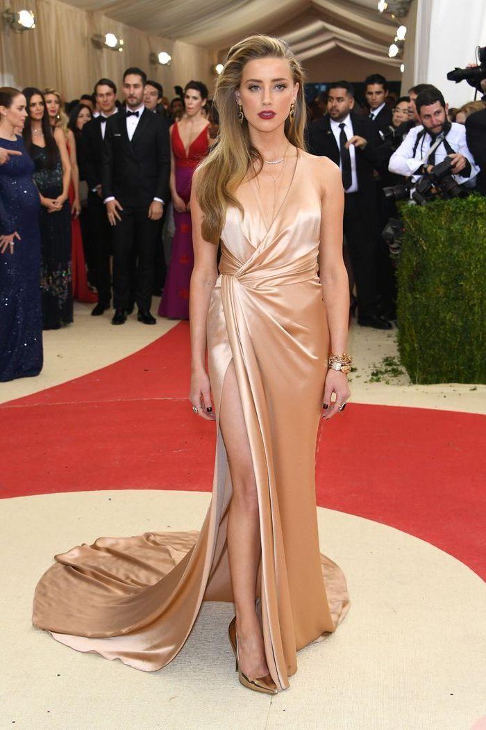 long wavy hair, met gala 2017 theme, amber hears, with a nude satin dress, gold metallic heels