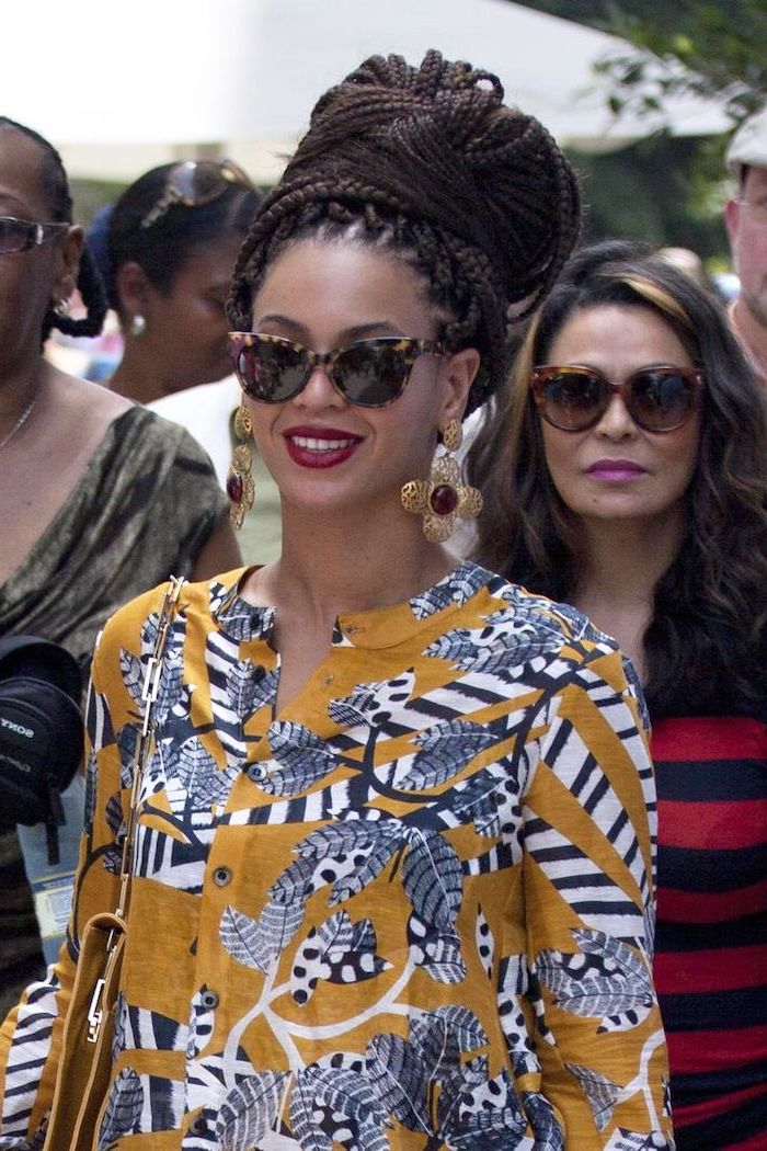beyonce wearing an african print dress, hair in a large bun, straight back braids, large flower earrings