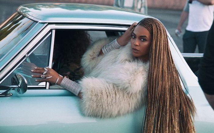 beyonce's formation video, showing out of a car, ghana braids, on long light brown hair, blue vintage car