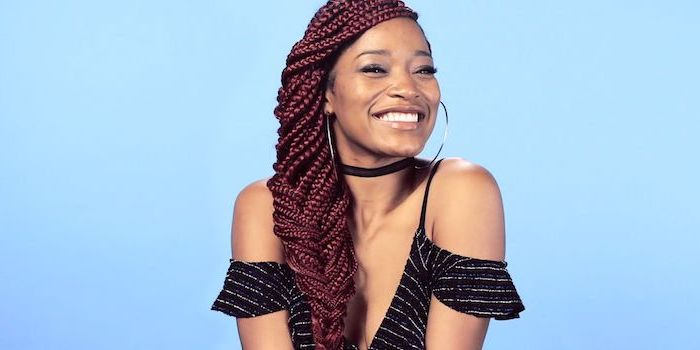 keke palmer smiling, red burgundy hair, ghana braids, in front of a blue background, wearing black top
