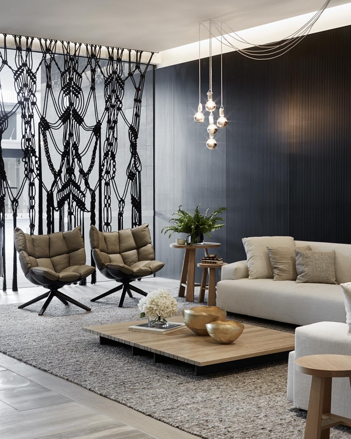 black accent wall, macrame wall hanging patterns, leather armchair, white corner sofa, wooden table