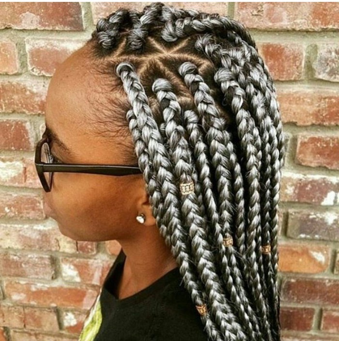 cornrows to the side, black and ash grey hair with beads, woman standing in front of a brick wall