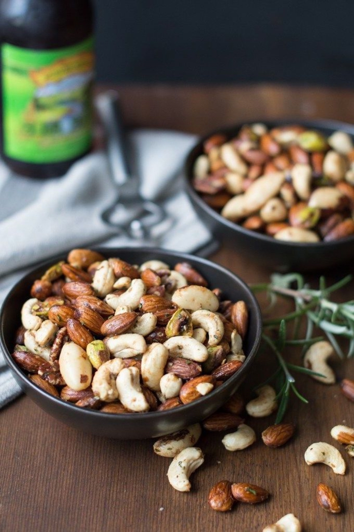 different types of nuts, inside black bowls, vegan hors d oeuvres, wooden table