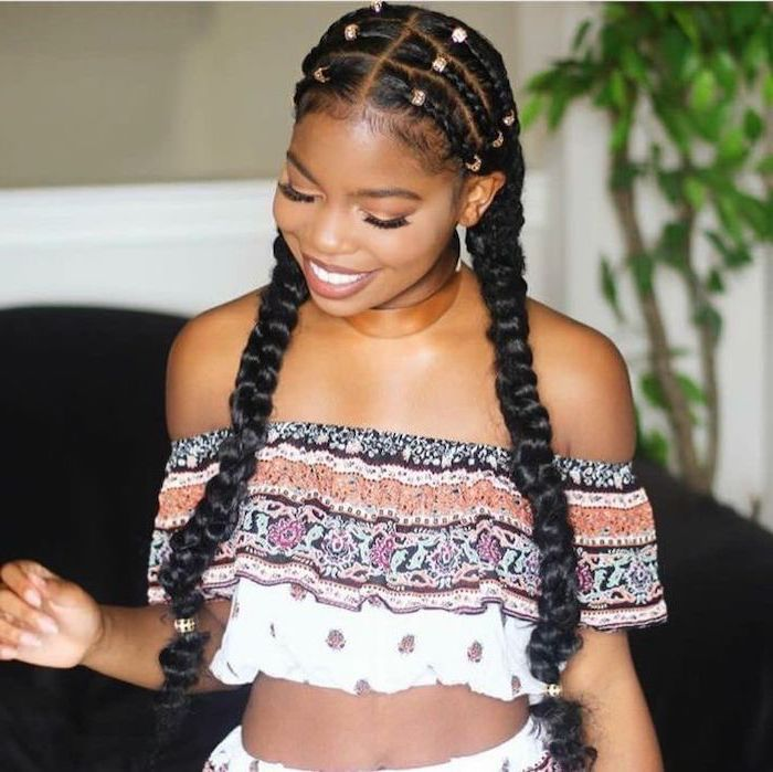 girl smiling, wearing a printed crop top, black hair, cornrows to the side, with beads
