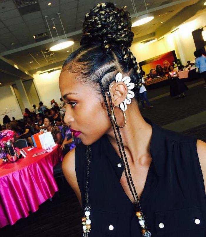 woman with black hair, in a bun with beads, female cornrow styles, wearing a black top