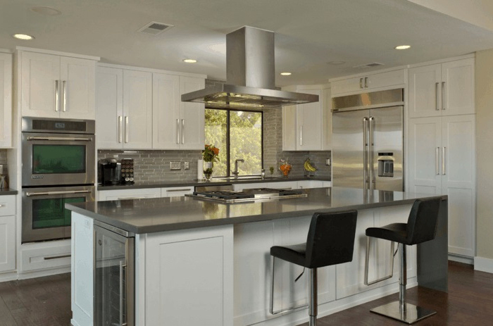 black leather chairs, white cabinets, kitchen island with sink, wooden floor, grey tiles backsplash