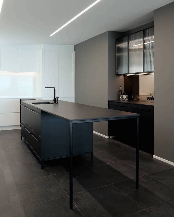 small kitchen island with seating, black metal table, black cabinets and drawers, black tiled floor