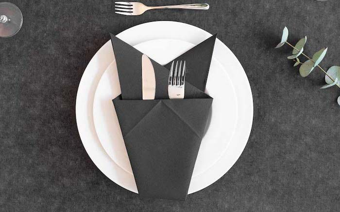 thanksgiving napkin folding, black napkin, silverware inside, on white plates, on a black table cloth