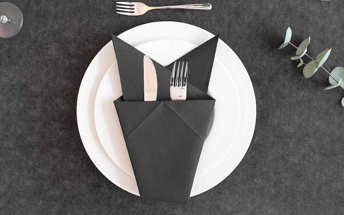 thanksgiving napkin folding, black napkin, silverware inside, on white plates, on a black table cloth