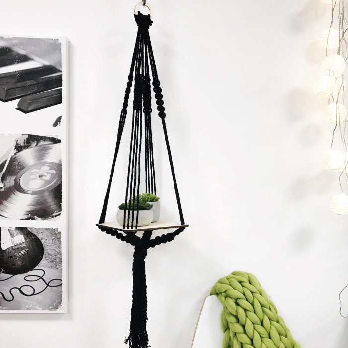 black plant hanger, free macrame patterns, white wall, knitted green blanket, potted plants