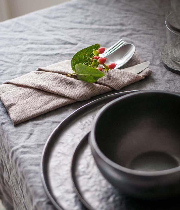 grey table cloth, beige folded napkin, silverware inside, thanksgiving napkin folding, black bowl and plates