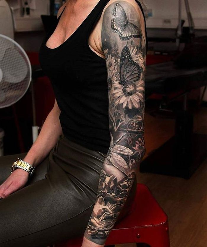 arm sleeve tattoo, chest tattoos for women, butterflies and flowers, black top, black leather pants