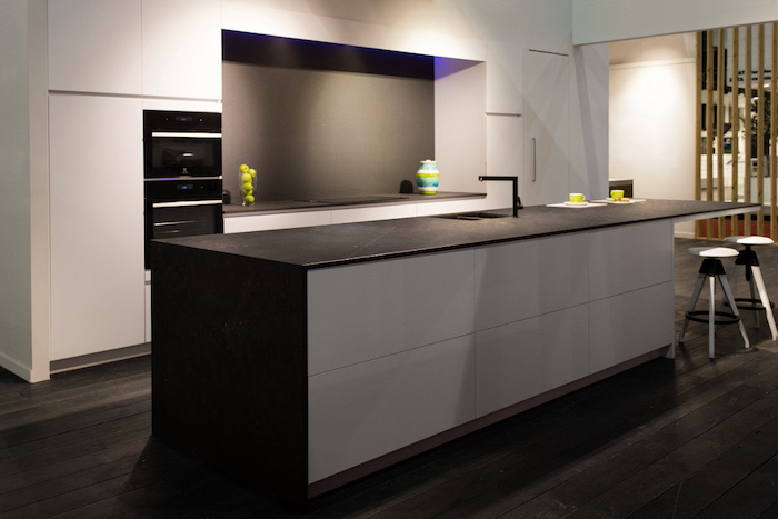 dark wooden floor, small kitchen island with seating, black countertops, grey backsplash, white cabinets