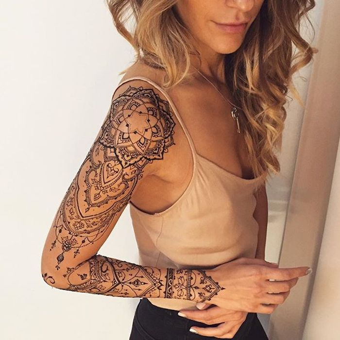 mandala flower tattoo, arm sleeve tattoo, small tattoos for girls, beige top, black pants, blonde hair