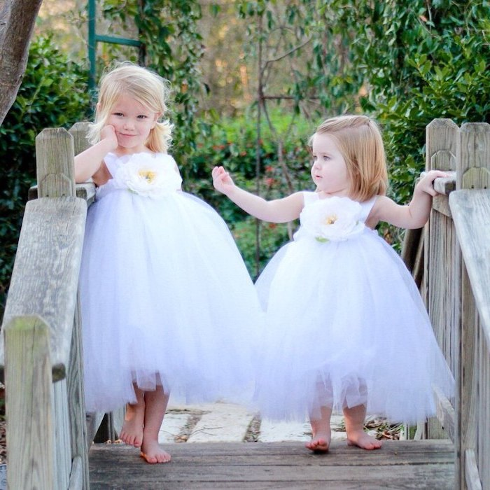 two girls, standing on a wooden bridge, dresses in white tulle dresses, flower girl dresses, short blonde hair