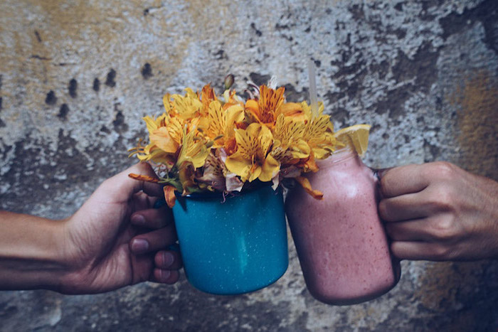 yellow flower bouquet, in a blue metal vase, banana smoothie recipe, lemon slice on the rim