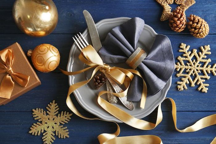 blue napkin with ring, napkin folding, golden ribbon, on a grey plate, with silverware, christmas ornaments