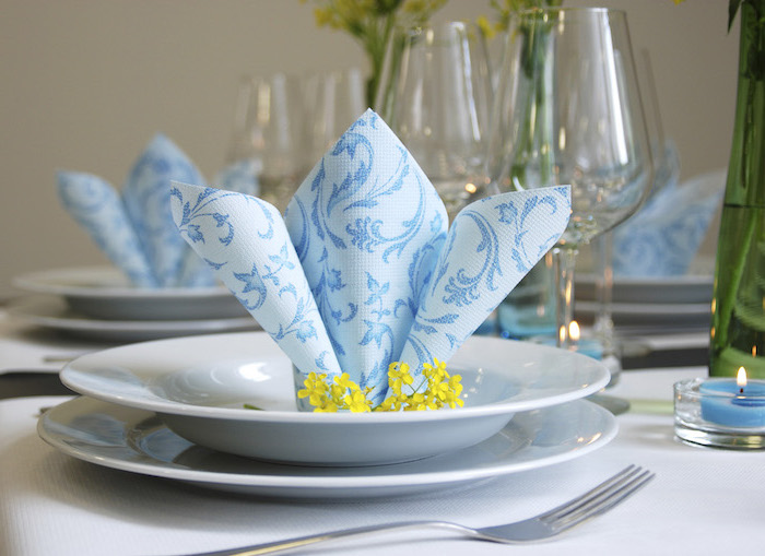 blue napkin, yellow flowers, in a white plate, easy napkin folding, wine glasses around
