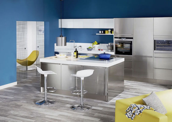 yellow sofa, blue walls, small kitchen island with seating, white bar stools, metal kitchen island and cabinets