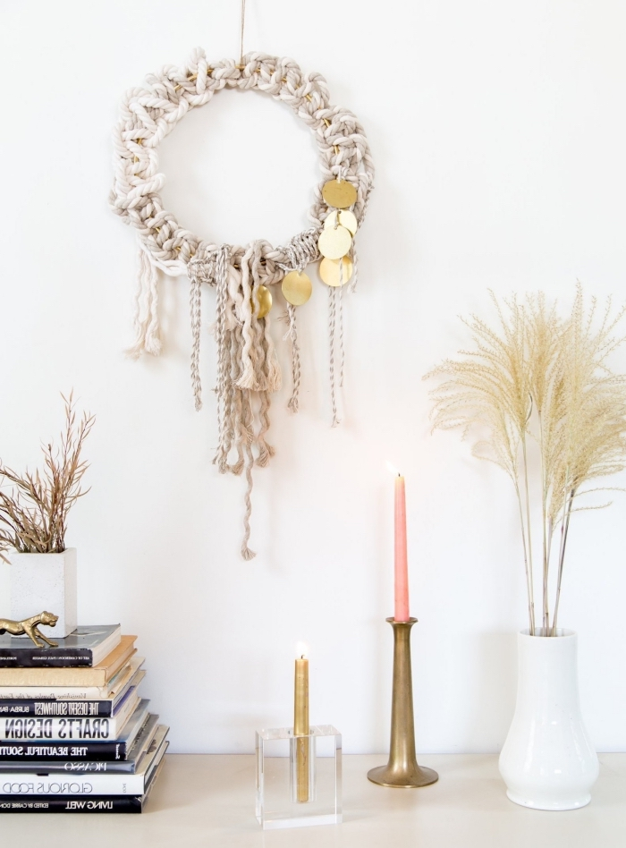 white wall, white ceramic vase, large macrame wall hanging, stack of books, pink and cold candles