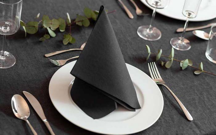 black folded napkin, on a white plate, silverware arranged around it, easy napkin folding