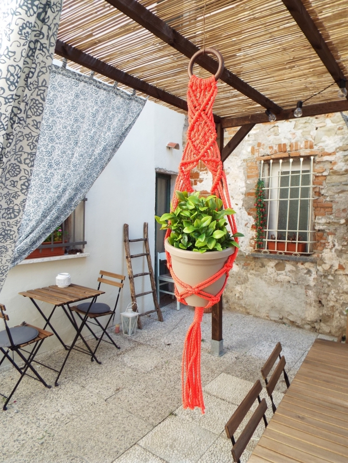 brick wall, wooden garden furniture, large macrame wall hanging, red plant hanger, tiled floor