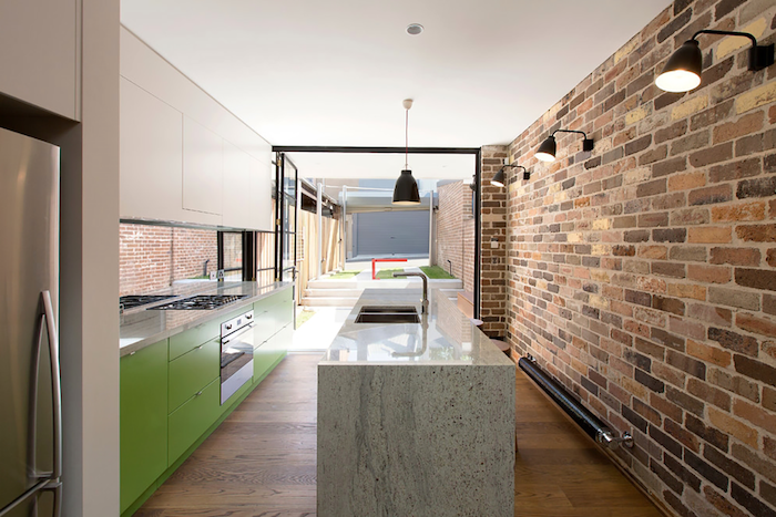 brick wall, green cabinets and drawers, granite countertop, small kitchen island with seating, wooden floor