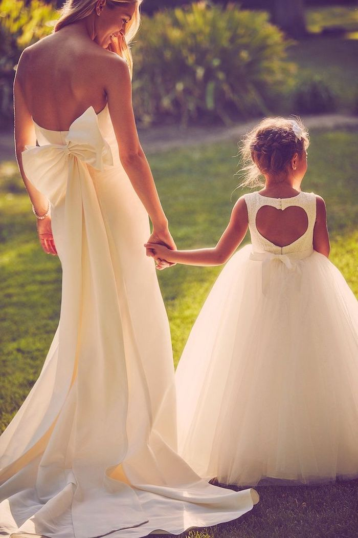 bride holding hands with flower girl, flower girl dresses, white dresses, heart shaped back, tulle bottom