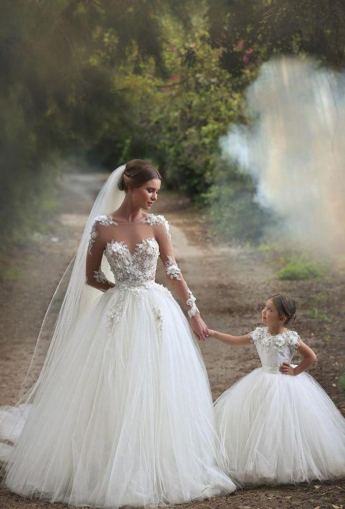 bride holding hands with a flower girl, dresses for girls, white lace and tulle dresses, on a pathway