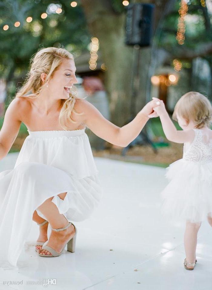 bride and toddler flower girl dancing, white lace and tulle dress, dresses for girls, white tiled floor