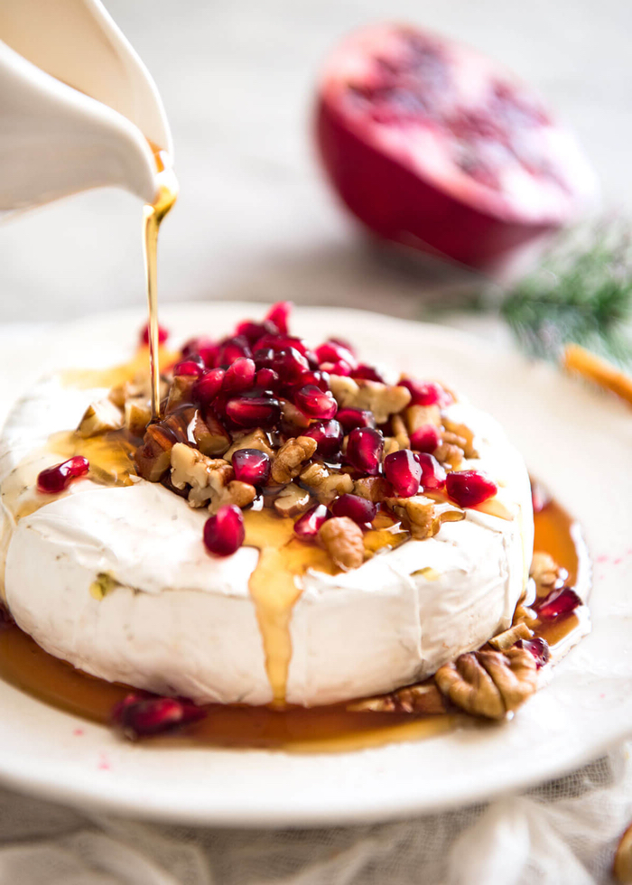 brie cheese, with honey and pomegranate, chopped nuts, dairy free appetizers, white plate