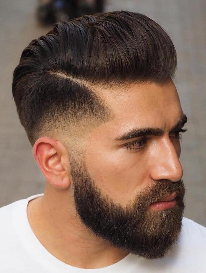 brown hair, short sides long top haircut, black beard, white shirt