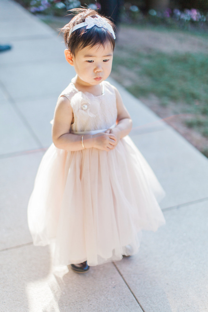 toddler girl, with a pixie cut, light pink tulle dress, girls party dresses, tiled floor, light pink diadem