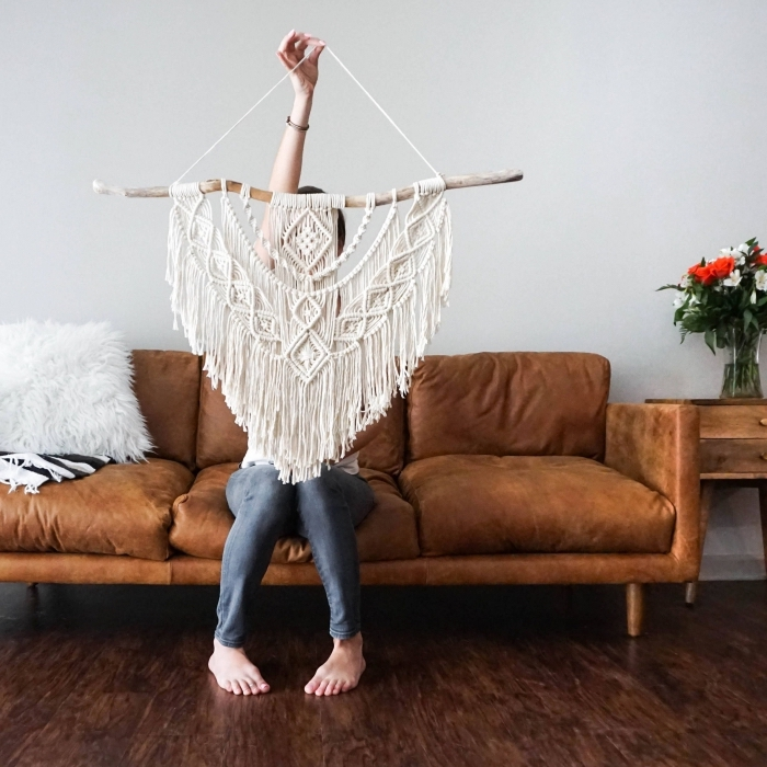 large macrame wall hanging, brown velvet sofa, woman sitting on it, wooden floor, white wall